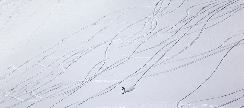 Panoramic view on snowboarder downhill on off piste slope with n