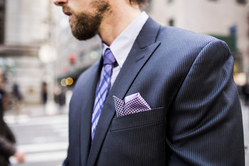 Midsection of well-dressed businessman standing on city street