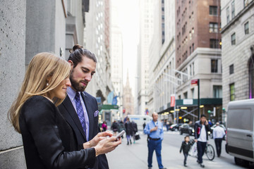 Woman showing phone to businessman against buildings in city