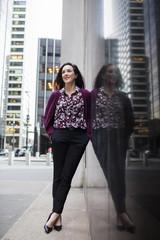 Confident businesswoman standing on sidewalk by glass window