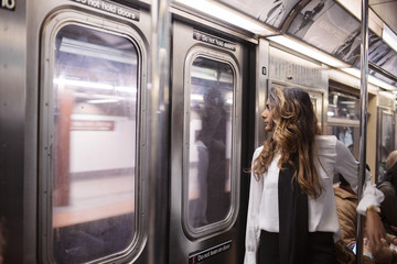 Businesswoman looking through window while traveling in subway train