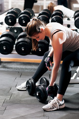 Training with dumbbells young woman, close-up. Attractive female athlete workout with dumbbell at gym. Bodybuilding, armwrestling, fitness concept