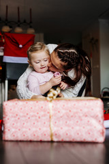 Mother kissing daughter during Christmas celebrations