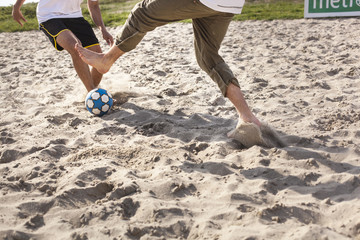 Low section of men playing soccer at beach
