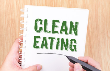 clean eating word on white ring binder notebook with hand holdin