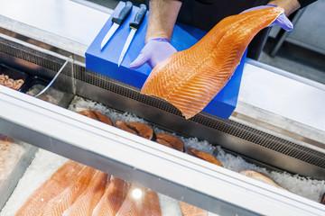 Cropped image of fish vendor holding salmon at supermarket