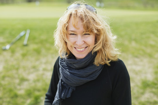 Portrait of cheerful woman at golf course