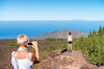 Back view of mother taking a picture of daughter on a mountain s
