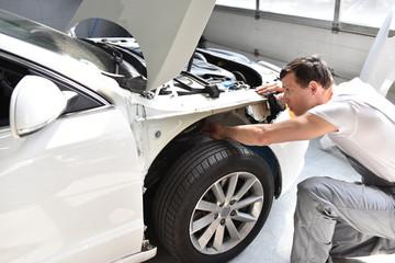 Reparatur einens Unfallwagens durch Mechaniker in der Werkstatt