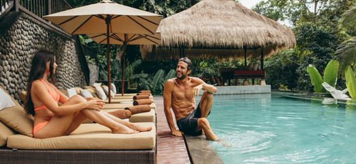 Couple relaxing at resort swimming pool