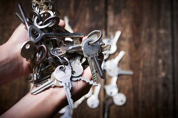 Hands holding an old metal keys and lock.