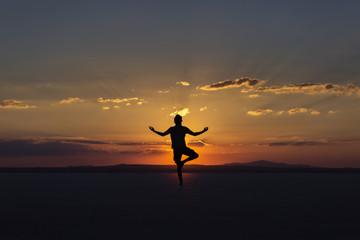 Yoga posture on sunset by man
