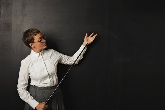 Female teacher with pointer at blackboard