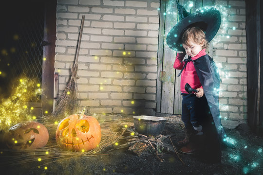 Little witch making a magic potion at Halloween night. Horror.