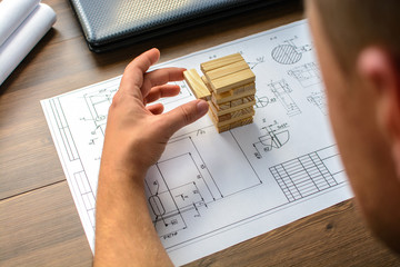 The man (businessman, architect) draws a plan, graph, design on large sheet of paper at office desk and builds model house from wooden blocks