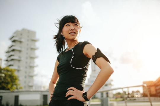 Young womantaking a break during morning run
