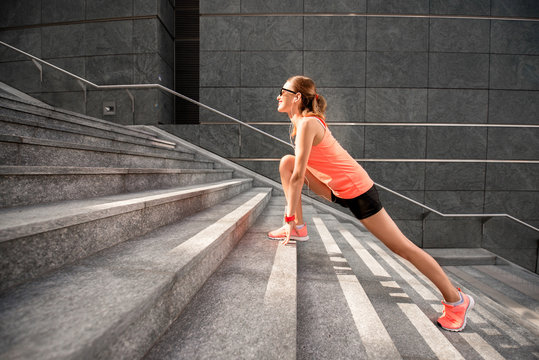 Young sports woman stretching legs on the stairs in the modern city. Healthy lifestyle in the big city.
