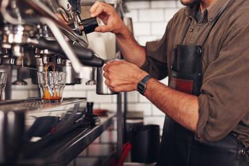 Barista making coffee using a coffee maker