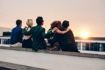 Friends relaxing on terrace in evening