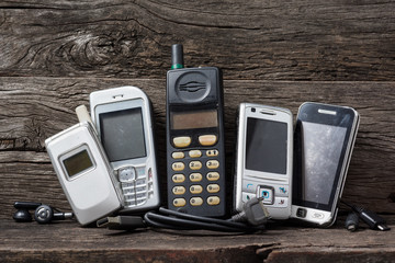 old and obsolete mobile phone and accesories on old wooden shelf Wall mural