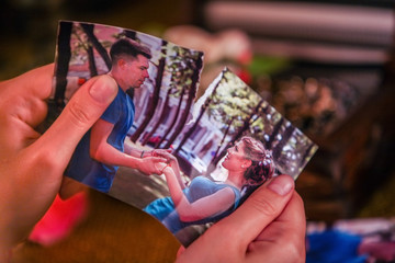 Female hands tearing love photos. Love is gone. On pictures couple in love.