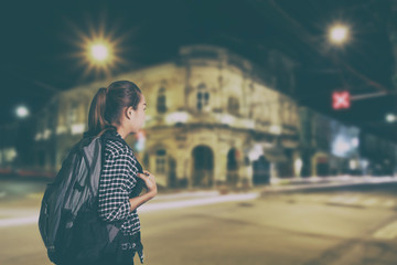 Traveling asian woman with backpack on dark night ,vintage style