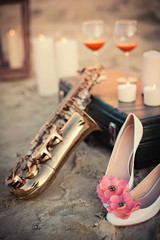 stylish shoes with flowers and saxophone  lying on the beach