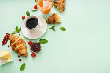 breakfast time with croissants and coffee on green table