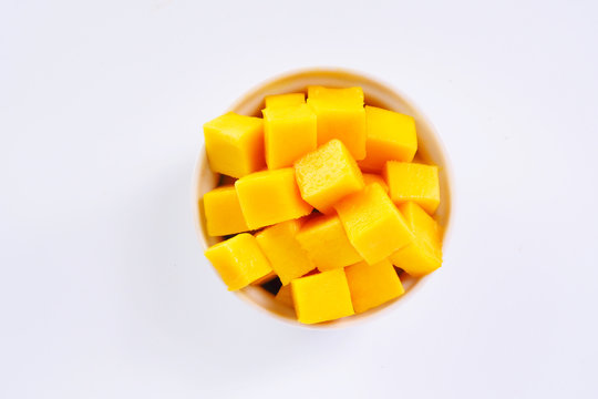 Top view of diced ripe mango cube in a white bowl on a white background.