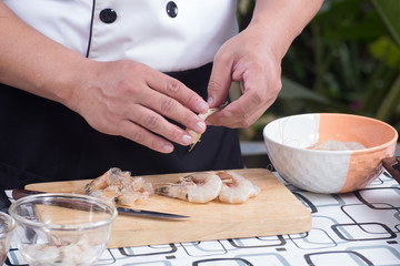 Chef peeling shrimp before cooking