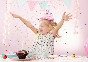 Cheerful child playing with colorful confetti in decorated room. Concept of birthday celebration and party.