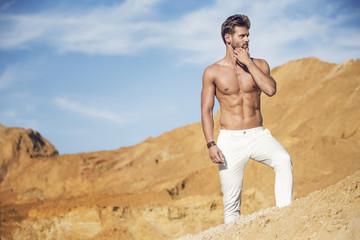 Handsome well-built man walking in the desert