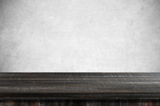 Empty dark wooden table over gray cement wall background