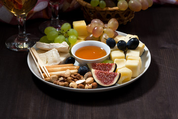 plate of cheeses, snacks, fruits and wine on a dark background