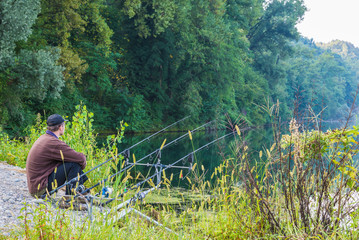 Fishing adventures. Fisherman sitting near the fishing rods waiting to catch a fish