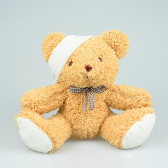 Conceptual Sick Brown Teddy Bear with Bandage on the Head isolated on white background