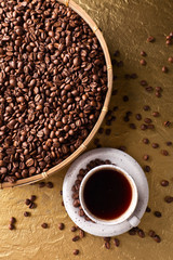 Cup of black coffee and  beans on a golden background