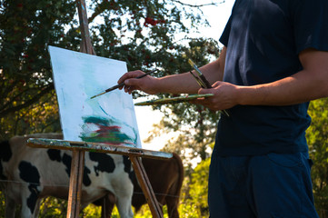 Man painting a picture of cows in the open air