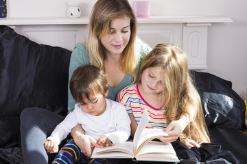 Mother reading to kids in bed
