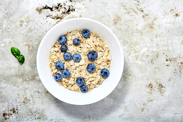 Raw oat flakes topped blueberries in white bowl