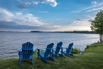 row of blue wooden cottage chairs facing lake