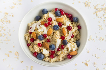 A bowl full of oatmeal, blueberry, red currant, coconut and almond. Healthy breakfast for kids and adults. Minimal style.