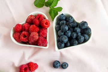 Picture of two heart shaped plate filled with blueberries and raspberries and mint leaves.