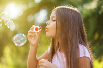 Children girl blowing soap bubbles in outdoor forest