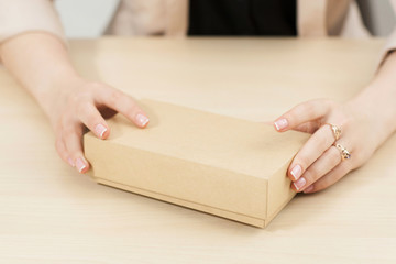 Female hands holding carton box on table. Unrecognizable woman preparing to open her parcel at home. Delivery service. online shopping, parcel opening concept