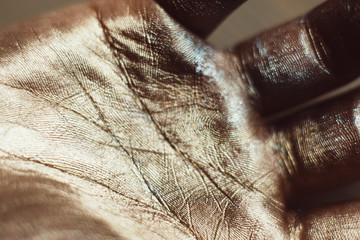 Close-up photo of golden human hand. Patterns on painted palm with gold dust. Luxury design of greasepaint, ceremonial body art