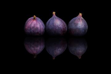 Three fresh purple figs on a black reflective background