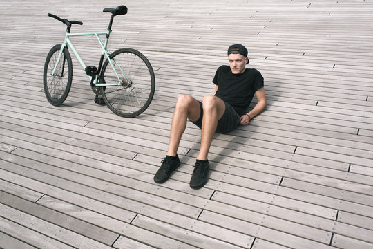 Stylish boy in cap sitting on wooden background with his bike parked beside