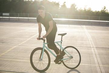 Young man riding bike Fototapete