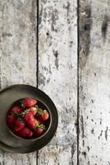 Overhead view of strawberries in bowl on wooden table